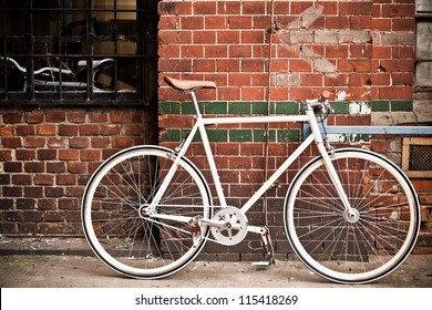 City bicycle fixed gear and red brick wall, vintage bike. Retro stylish cycling in town, old retro bike, cycling or commuting in city urban environment, ecological transportation concept