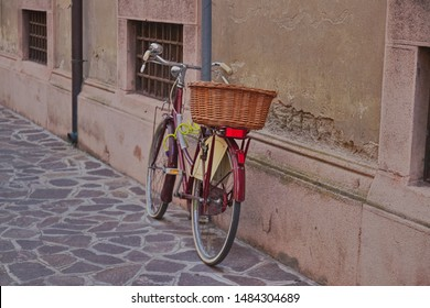 City bike with a basket stands against a stone wall in the city, Europe, Italy