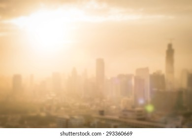City blur background of morning gold light view over cityscape downtown Bangkok with bright sun flare and bokeh summer cloudy sky
