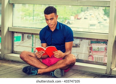City Boy. Way to Success. I Love Reading. African American college student sitting cross legged on floor against glass wall on campus, looking down, reading red book. Street, many cars on background.