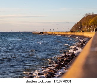 City breakwater in the morning sunlight. Calm sunrise at the city coast. Marine architecture.