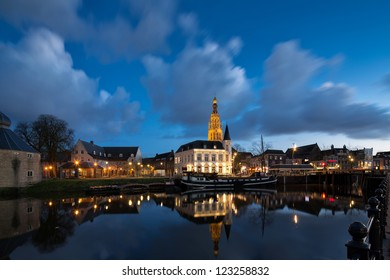City of Breda, Netherlands, at night, showing the beautifully lit tower of the big church in the center of the city with clouds in the sky
