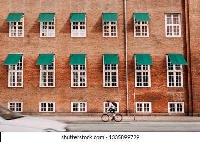 City with brick houses and cyclists driving on historical streets of Copenhagen, Denmark. One of the bicyclist in front of urban area facade.