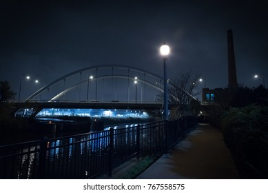 City bridge and urban industrial building with smokestack and riverwalk promenade by the Chicago river at night.