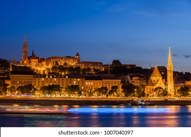 City of Budapest at night, cruise boats light trails on Danube river, skyline of the Buda side, Hungary.