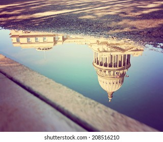 a city building reflected in the puddle toned with a vintage instagram filter