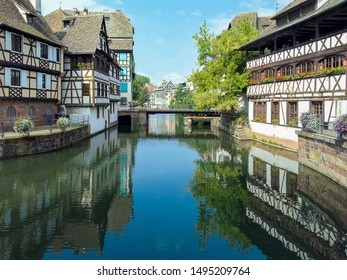 city buildings and bridge reflected in canal water in Strasbourg France