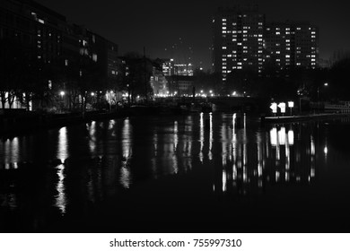 city buildings by the river in the night