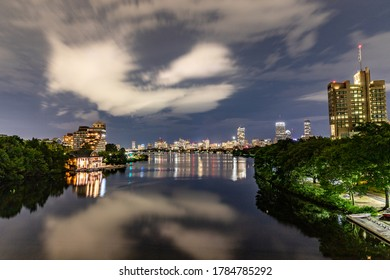 City buildings and clouds reflecting in river water below.