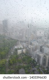 City buildings and the green of trees are just visible through a rain-smeared window. Rain drops are running down the pane.