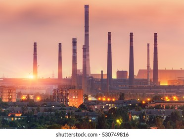 City buildings on the background of steel factory with smokestacks at sunset. Metallurgical plant with chimney. steelworks, iron works. Heavy industry. Air pollution, smog. Industrial landscape