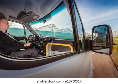 city bus driver on a sunny road in the middle of greenhouses