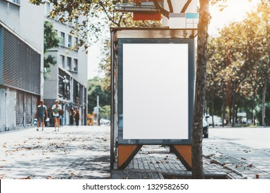 A city bus stop with the clean placeholder template; advertising empty poster mock-up in urban settings; a blank white banner mockup on the wall of the stop of a public transport near the road