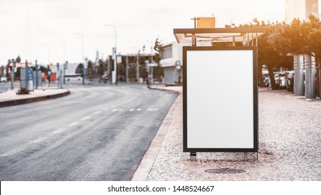 City bus stop on with an empty banner mock-up; template of an advertising banner on the stop of public transport; blank information placeholder mockup in urban settings on the pavement near a road