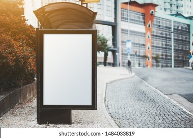 City bus stop on with an empty poster mock-up; template of an advertising banner on the stop of transport in a residential district; blank placeholder mockup on the pavement near a road with marking