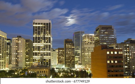 The city of Calgary at night with full moon, city skyline with modern skyscrapers and office space