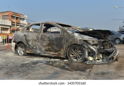City Car Burned.Burnt car with small flames inside of the engine