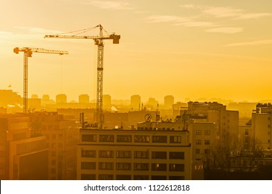 CITY CENTER, POLAND - DECEMBER 13, 2016: Orange smoky sunrise in winter Warsaw - cityscape with construction cranes and buildings.