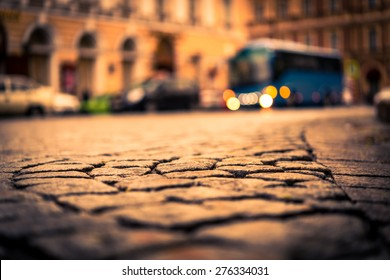 City central square paved with stone after a rain on which riding bus. View from the pavement level, image vignetting and the yellow toning