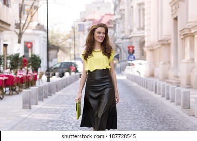 City chic girl with neon blouse and leather skirt