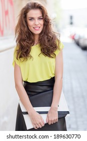 City chic young woman wearing a neon blouse and black leather skirt on beautiful city streets