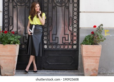 City chic young woman wearing a neon blouse and black leather sk