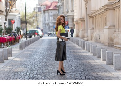 City chic young woman wearing a neon blouse and black leather skirt.