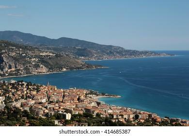 city coastline by sea beach residential buildings against high mountains on blue skyline background