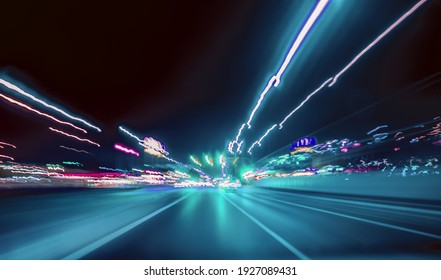 City colorful night lights perspective blurred by high speed of the car. A streak of light, trails.