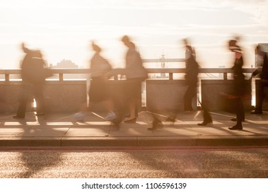 City commuters. High key blurred image of workers on London Bridge at sunrise. Unrecognizable faces. London, UK.