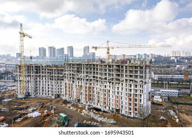 city construction site with yellow tower cranes and machinery. aerial top view of residential construction area.