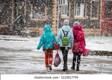 the city was covered by a snow storm, cold, climate change, movement is paralyzed because of the snow people move to the snowstorm on foot, hiding umbrellas and hoods, abnormal winter, precipitation