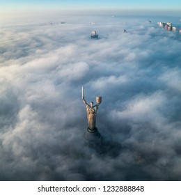 The city is covered with thick fog and protruding from it where neither where high-rise buildings and the monument Motherland. City in the mist