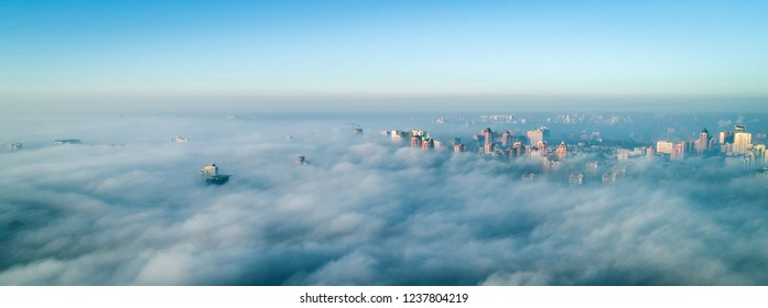 The city is covered with thick fog and protruding from it where neither where high-rise buildings. City in the mist