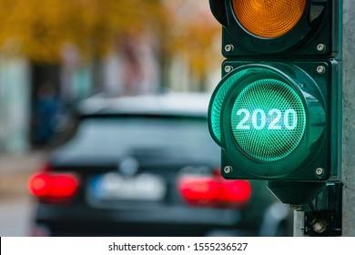 Eine Stadt, die mit einem Semaphor überquert wird. Grünes Licht mit Text 2020 im Semaphor. Neujahrskonzept - Bild