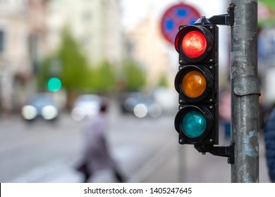 A city crossing with a semaphore. Red light in semaphore.
