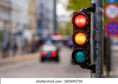 a city crossing with a semaphore, red and orange light in semaphore, traffic control and regulation concept