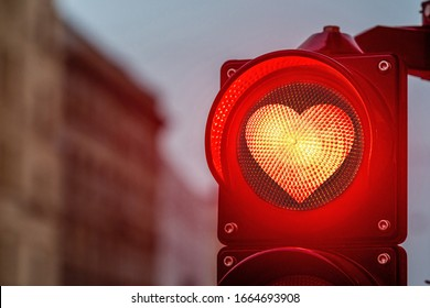 A city crossing with a semaphore,  traffic light with red heart-shape in semaphore - image