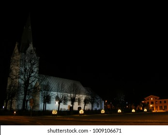 City Dobele, country Latvia. Winter landscape in the central square of the city. Lutheran church, illuminated at night. City Christmas decorations, darkness contrasts versus lantern lighting.