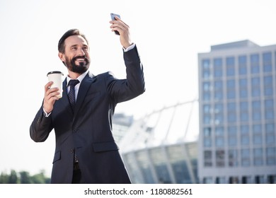 City dweller. Cheerful bearded businessman making photos of his city while drinking coffee in the morning