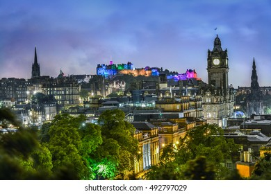 The city of Edinburgh at night with Edinburgh Castle illuminated in different colors. The stunning view was from Calton Hill - a hill in central Edinburgh, Scotland, situated near Princes Street.