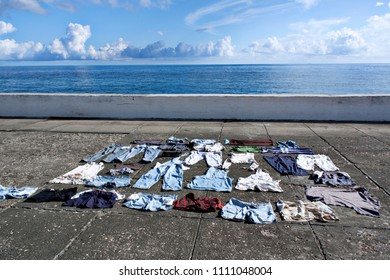 City embankment with clothes lying on hot concrete and drying out in bright tropical sunlight of Baracoa, Cuba