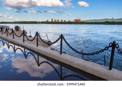 City embankment of the Yenisei River in Krasnoyarsk, Russia. The sky and anchor chain fences are reflected in a rain puddle. Urban landscape of the city of Krasnoyarsk on a summer day.