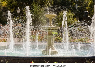City fountain. Fountain in city park on hot summer day. stream of water, drops and bright splashes of water in beautiful city fountain