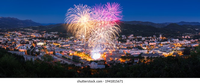 The city of Gap with July 14th Fireworks (Bastille Day celebration) in the Hautes-Alpes in Summer at twilight. Hautes-Alpes, France
