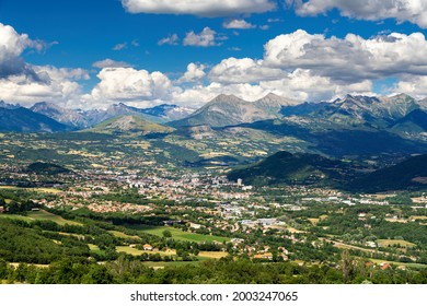 The city of Gap in Summer with view of the distant mountains of the Ecrins National Park massif. Hautes-Alpes in the French Alps. France - Shutterstock ID 2003247065