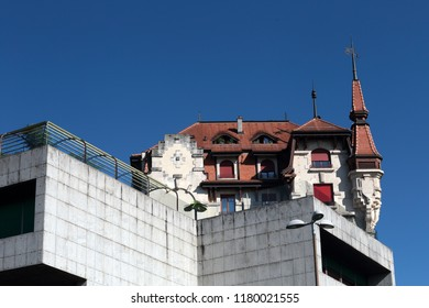 in the city of geneva in switzerland, the cohabitation of several architectural styles, old very art deco and modern raw concrete with hard lines, on a plain blue sky background