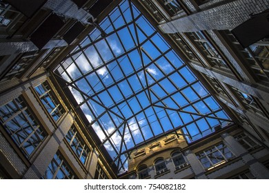 City geometry, a view from the inside to the sky from the yard. Four closing walls of a brick house, square of the sky. Modern and abstract architecture.