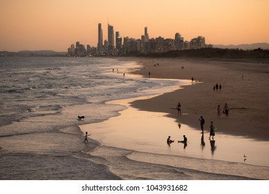 City of Gold Coast, Queensland, Australia with families enjoying the beach in the foreground.
