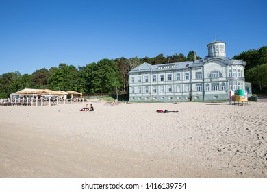 City Jurmala, Latvian Republic. Peoples walking on sand beach. Urban view with tourists and buildings.Travel photo. 2019. 4. Jun